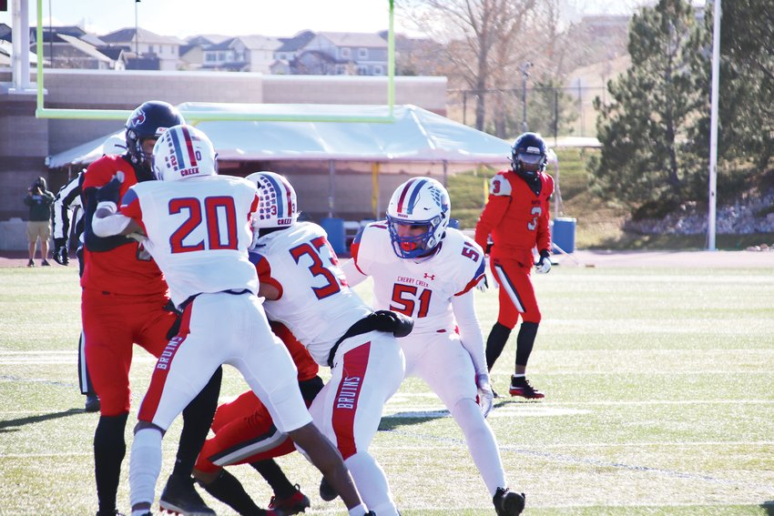 Cherry Creek's defense surrounds an Eaglecrest runner. Al Ashford III (20), Luis Lozano (33) and Thomas Fischer (51) are the Bruins defenders.