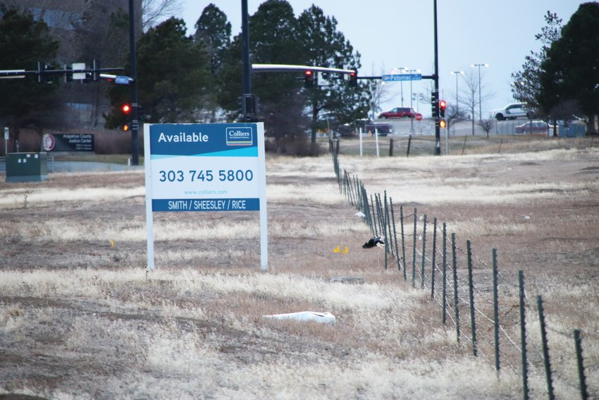 A real-estate availability sign sits near a short fence that lines a piece of land where a small number of animals live. In the background is the Arapahoe County Justice Center, where the Arapahoe County District Court operates.