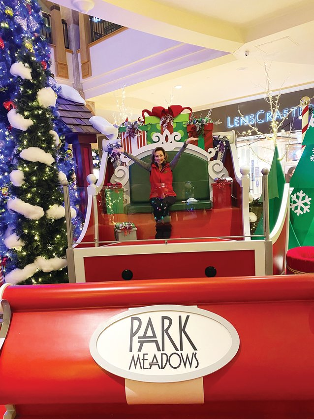 Pam Kelly, senior general manager for Park Meadows, sits atop the new Santa sleigh the mall installed this year for its touchless Santa exhibit.