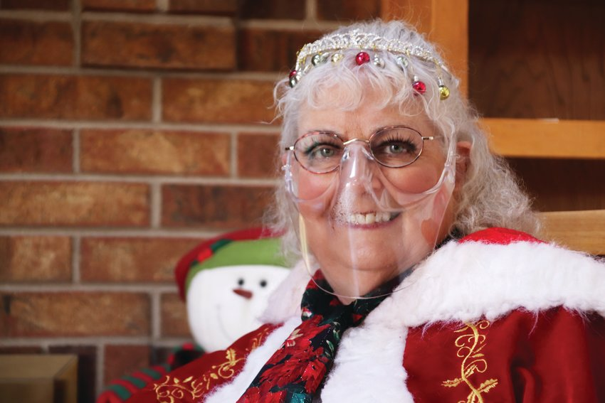 Mrs. Claus, portrayed by Kam Breitenbach, in a specially designed transparent, plastic face covering. The covering helps in photos — and, Breitenbach said, she doesn't want her makeup to go to waste.