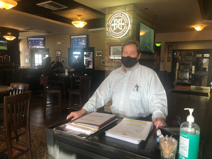 Chris Bogert, general manager at Landsdowne Arms in Highlands Ranch, stands behind the host desk at the restaurant just hours before indoor dining in the county became prohibited.