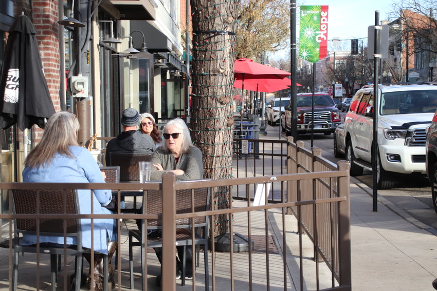 Diners sit outside Smokin Fins in downtown Littleton on Nov. 20, hours before new orders took effect ending indoor dining in the face of surging COVID-19 numbers.