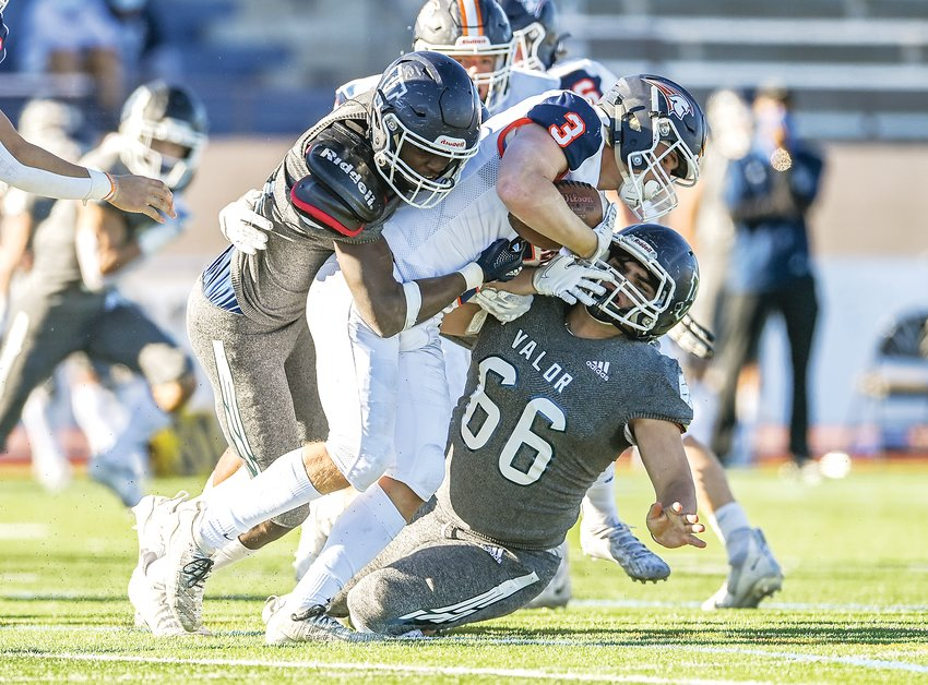 Legend's Connor Eise (3) gets wrapped up by Valor Christian defenders Cayden Hawkins (41) and Nick Chapdelaine (66). The Eagles ended the 5A semifinal with a 45-0 victory over the Titans.