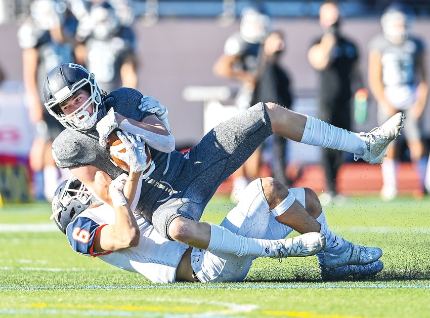 Legend's Jack Bruner (6) pulls Valor Christian's Tyler Larson (6) to the turf in the 5A Semifinal Saturday at Valor Stadium. The Eagles ended the game with a 45-0 victory over the Titans.