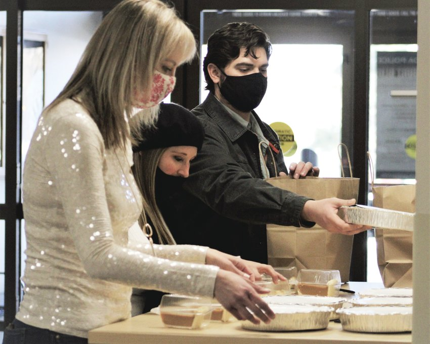 From left, Councilmember Lauren Simpson and Arvada residents Kimber and Josh Just lay out food on a counter at the Arvada Police headquarters on Thanksgiving Day. (Michael Hicks)