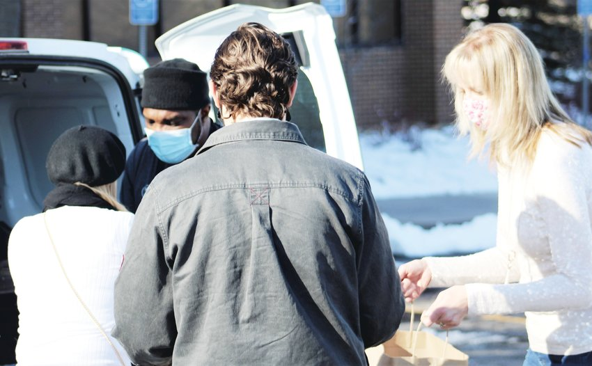 From left, Arvada residents Kimber Just, husband Josh Just and Councilmember Lauren Simpson receive bags of lunches from Footers Catering that they delivered to Arvada Police officers and Arvada firefighters on Thanksgiving Day. (Michael Hicks)