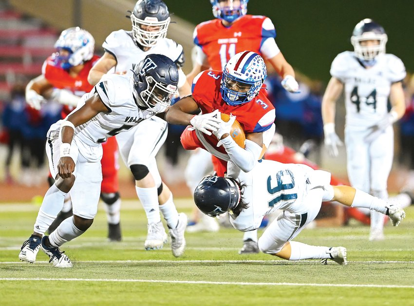 Cherry Creek's Myles Purchase (3) gets airborne as Valor Christian defenders Zaire Jackson (5) and Griffin Meier (16) cut him off. Purchase's Bruins shut out the Eagles 21-0 to win the 5A state final Dec. 5 at the CSU Pueblo Thunderbowl.