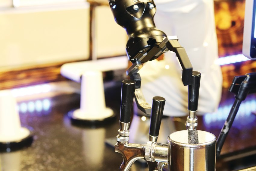 The Universal Robots robot arm at Robo Esso pushes a handle while making a latte.