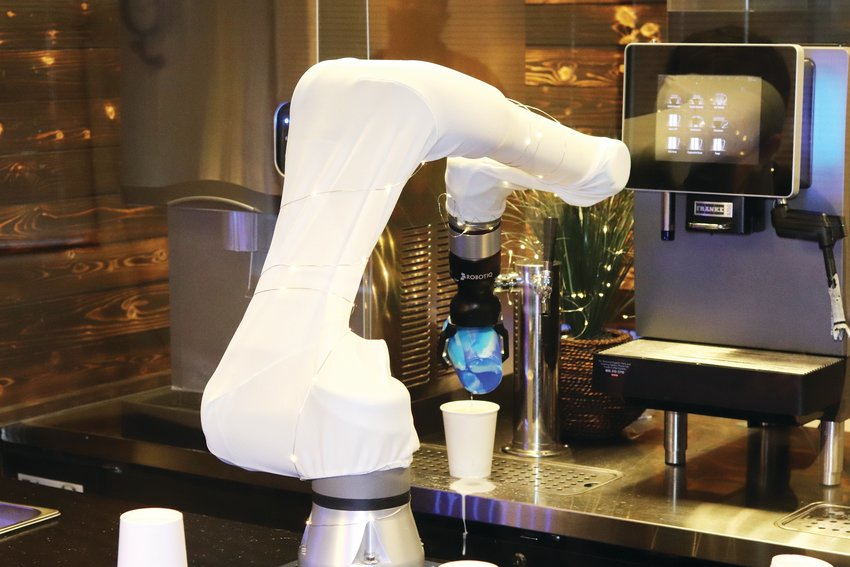 The robot arm pours a latte into a to-go cup.