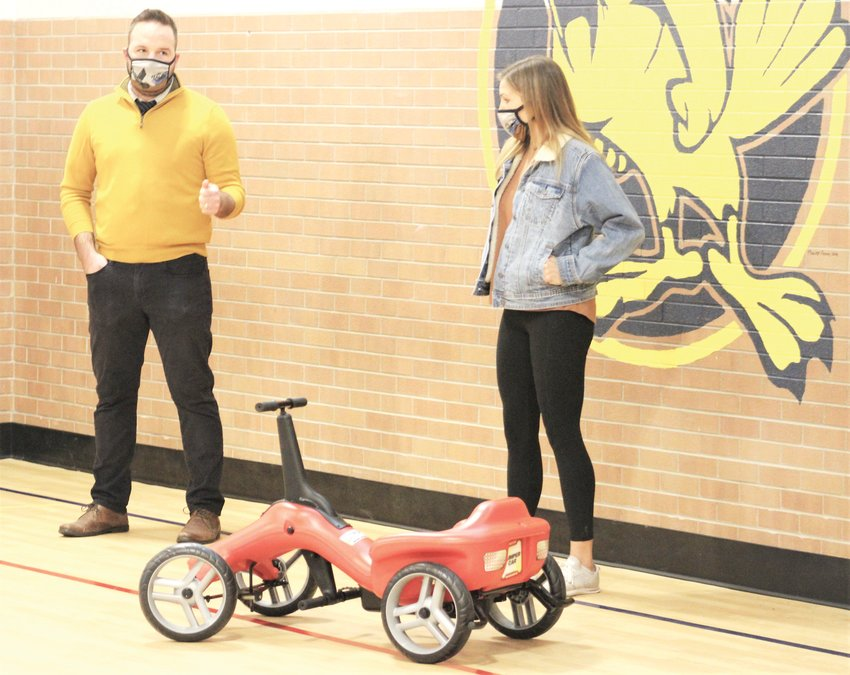 Adapted physical education teacher Katie Thompson, right, listens in as Fitzmorris Elementary School Principal Johnny Horton talks about the school's Pumper Car during a press conference on Dec. 7.