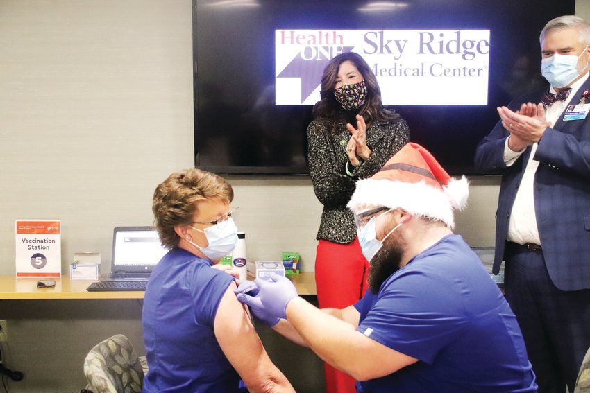 "Carol Knight receives the first shot of the Pfizer COVID-19 vaccine Dec. 16 at Sky Ridge Medical Center. Knight, a clinical nurse coordinator, has worked at Sky Ridge for 17 of her 30-year career. ""It's time,"" Knight said. ""It's time to start 2021 right."""