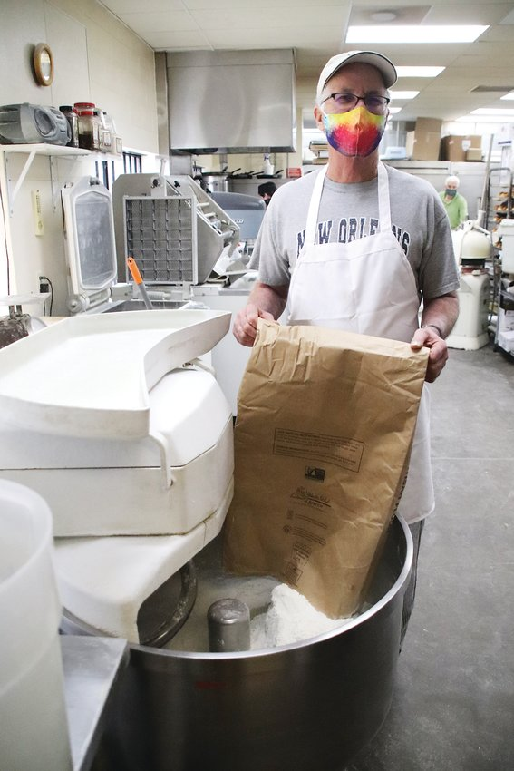 Trompeau Bakery head bread baker Rande Smith dumps flour into a mixer. Smith said while high elevation can make baking in Denver challenging, so can low humidity.