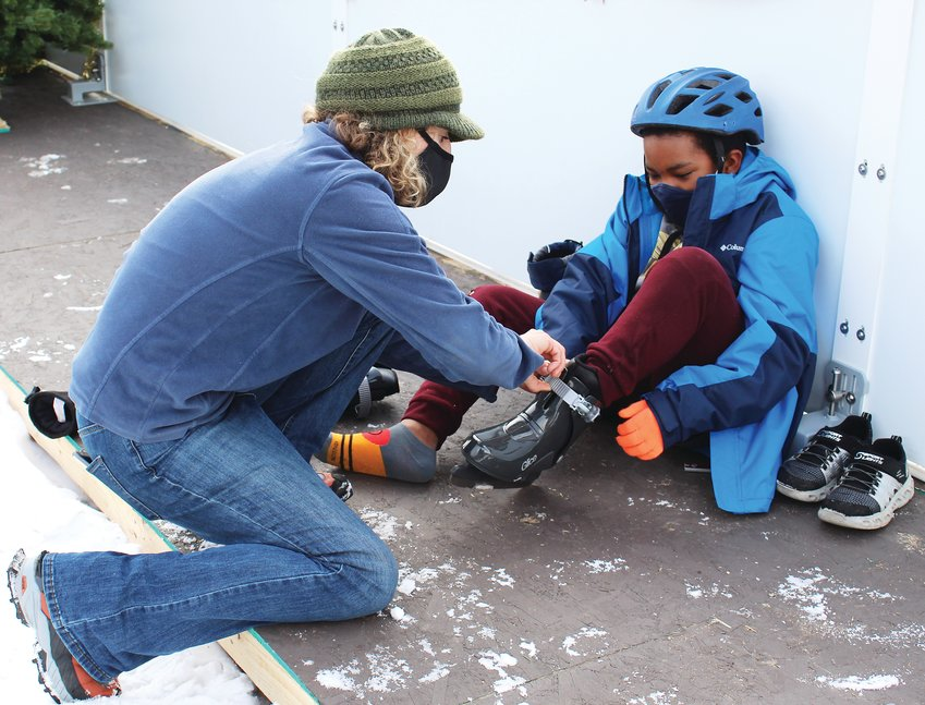 Samantha Dhyne, the rec district's project lead for the rink, helps Noah Windley, 11, with his skates on Dec. 18.