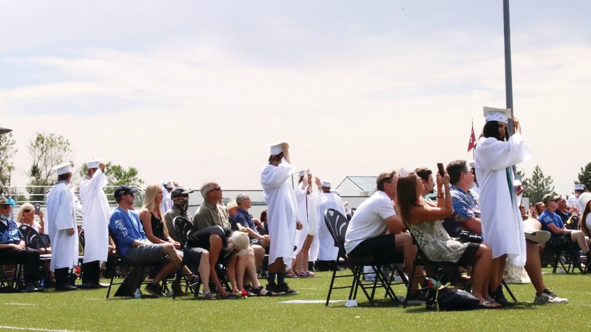 Graduates move their tassels while standing beside their families at the July 16 Faith Christian high school graduation ceremony.
