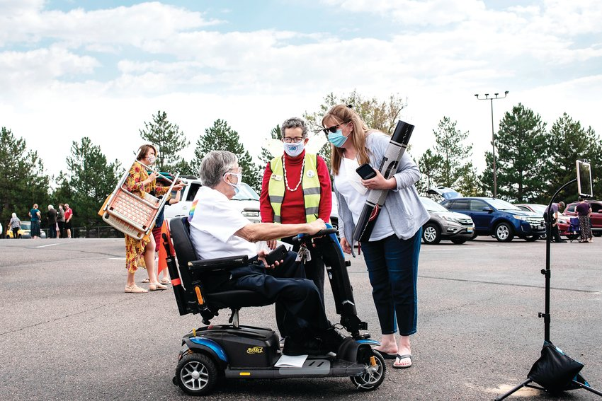 AUMC Members Ben and Maggie Roe speak with staff member Laura Winberg as they get their spot for AUMC's parking lot service.