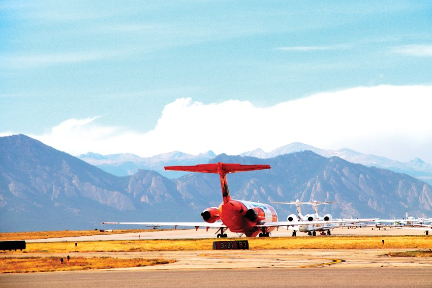 Smoke from the fires in Boulder County rise up over the mountains and an orange-and-white slurry tanker airplane Oct. 21 at the Rocky Mountain Municipal Airport.