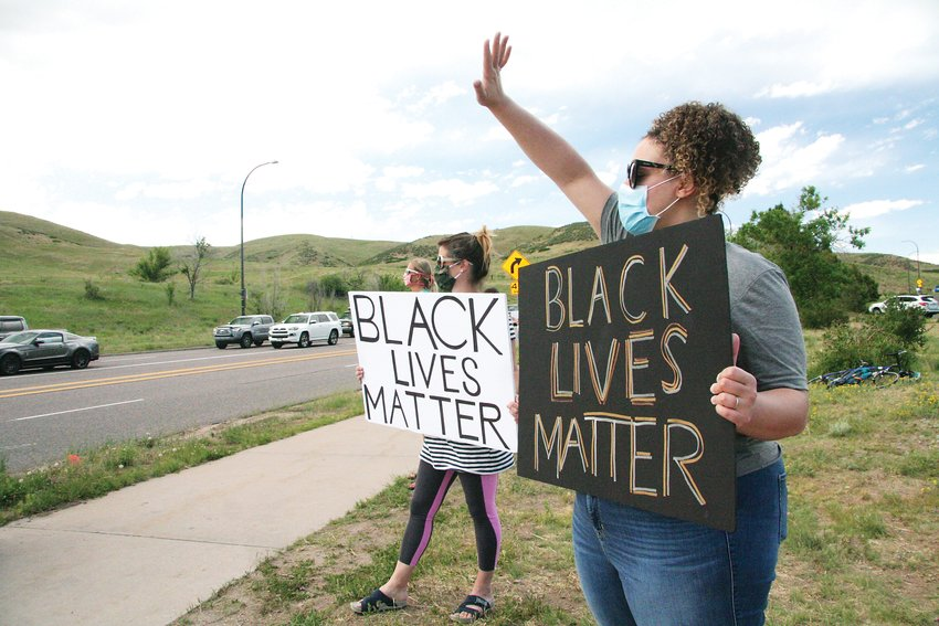 "Protest organizer Jocelene Smith waves to a passing car that was honking in support during the June 11 protest along the Alameda Parkway. Smith, a biracial woman, said she had deeply personal reasons to support the Black Lives Matter movement. ""My brothers are black men I fear for every day."""