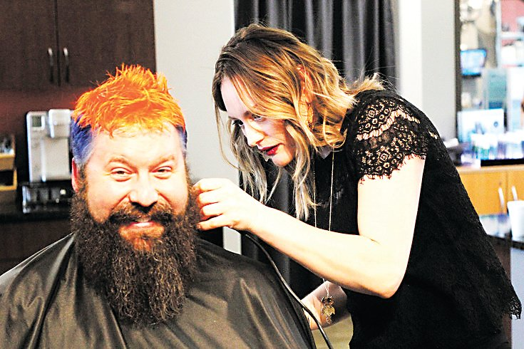 Mike Waid smiles as stylist Yadi Ordonez trims his newly-dyed hair in March 2016 at Haircolorxperts in Parker in March 2016. Waid dyed his hair to raise awareness for a St. Baldrick's Foundation childhood cancer research fundraiser.
