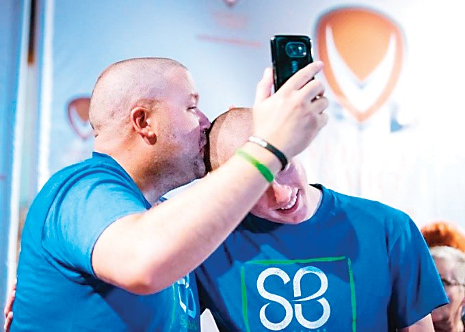 "Mike Waid, left, takes part in a St. Baldrick's Foundation ""Shave the Mayor"" fundraiser in 2018. Waid poses with his son Matthew, who began shaving his head alongside his dad in solidarity with the charity."