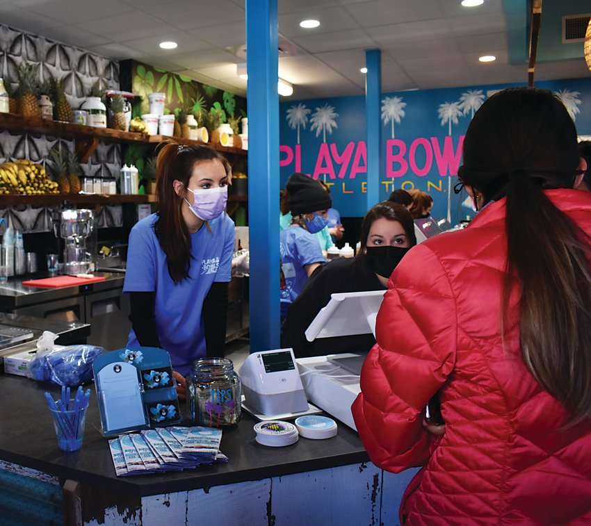 Employees take orders on opening day at Playa Bowls, a new shop in downtown Littleton.
