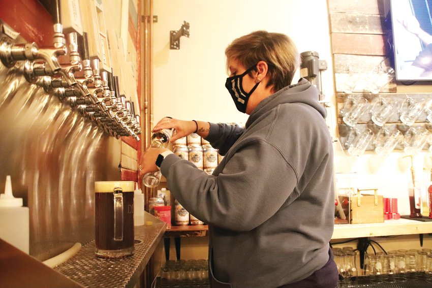 Sharon Murphy, co-owner of Welcome Home Brewery in Parker, pours a beer Jan. 7. Welcome Home received 5-Star certification to operate at 25% capacity in December.