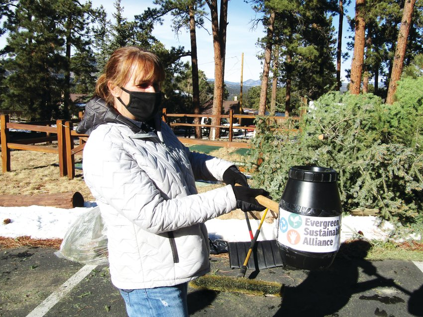 Deanna Baysinger holds a container on a stick that she used to collect donations for the Evergreen Sustainability Alliance during the Christmas tree recycling event at Evergreen Lutheran Church.