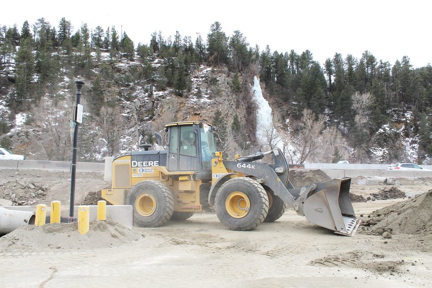 A front loader scoops up dirt Thursday in the parking area adjacent to The Vintage Moose in Idaho Springs. Several sections of the city's downtown parking lots have been blocked off for construction work related to the westbound mountain express lane project.