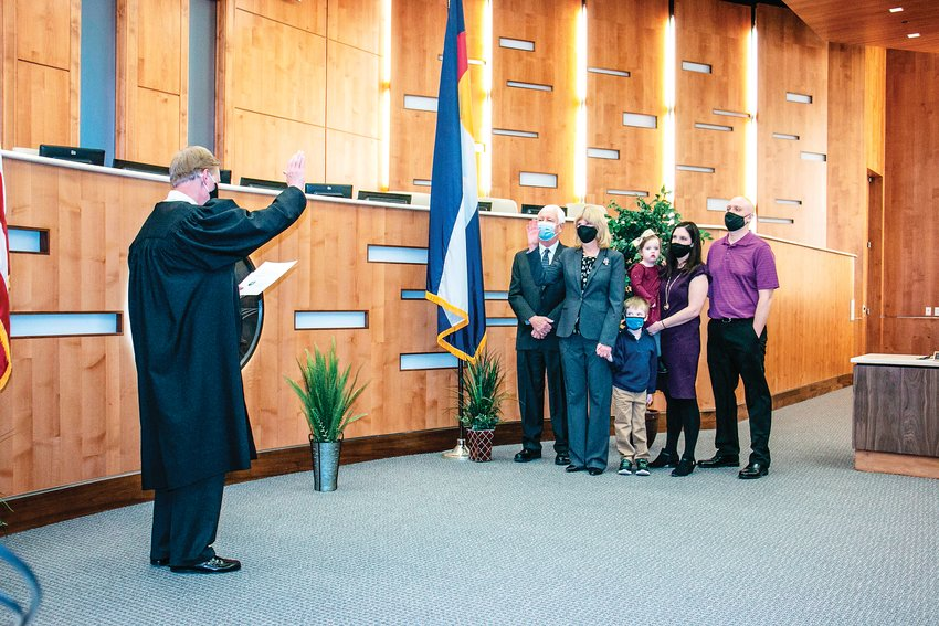 Commissioner Eva Henry swears her oath of office Jan. 12 in the Adams County building in Brighton while surrounded by family. The oath was performed by 17th Judicial District Chief Judge Don Quick. The virtual inauguration was socially distanced and shown via the Zoom networking platform.