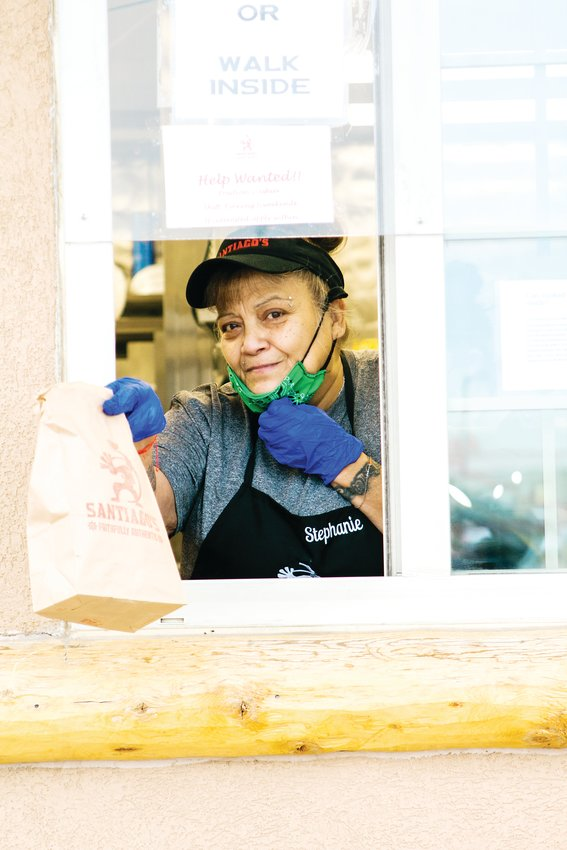 An employee working the Santiago's take-out window smiles for the camera in Brighton.