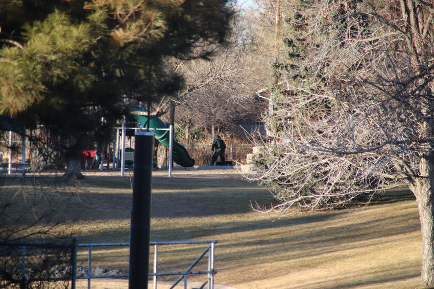 A bomb squad technician retrieves a package from Rotolo Park's playground on Jan. 20. The package was later found to be non-explosive.