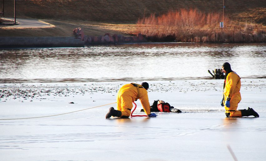 Thornton Firefighter/Paramedic Blake McCarthy crawls across to join Metro North Fire and Rescue Lt. Tom Willard on Thornton's Civic Center Park pond and onto the ice shelf Jan. 19. It was part of a joint training exercise between the Thornton department and the  North Metro Fire and Rescue District.