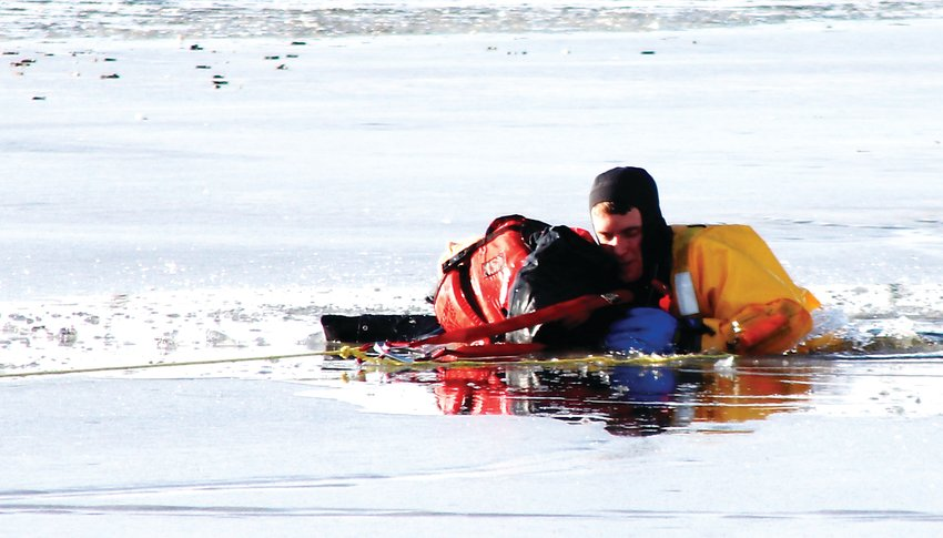 Thornton Firefighter/Paramedic Blake McCarthy struggles to lift a weighted dummy out of the freezing cold water of Thornton's Civic Center Park pond and onto the ice shelf Jan. 19. It was part of a joint training exercise between the Thornton department and the  North Metro  Fire and Rescue District.