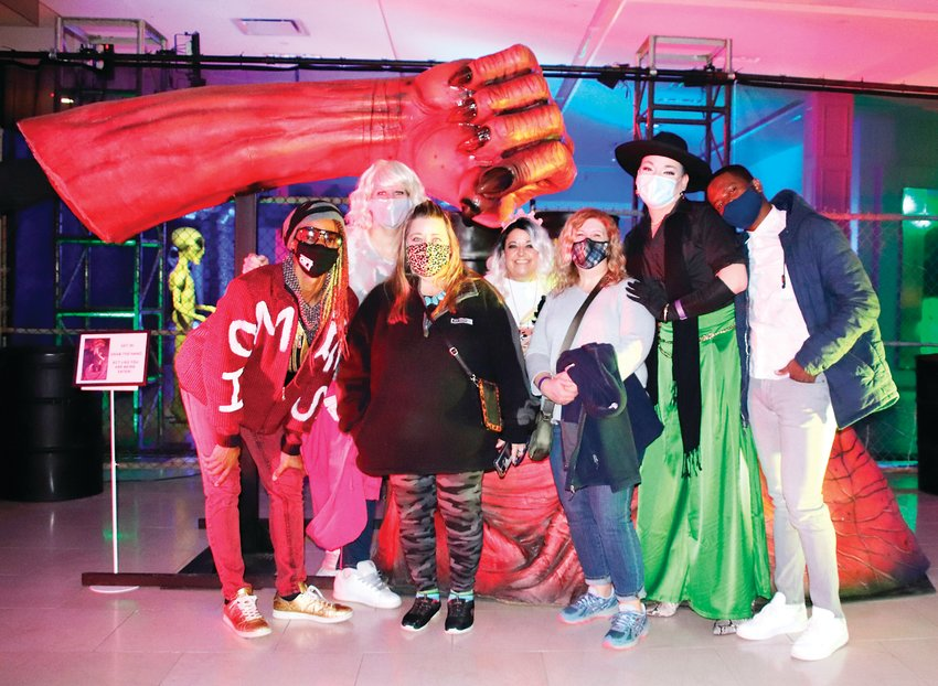 A group of friends gather for a photo in front of a display at Distortions Monster World. Masks must be worn while exploring the 19,000-square-foot space, but guests are permitted to remove them for photos.