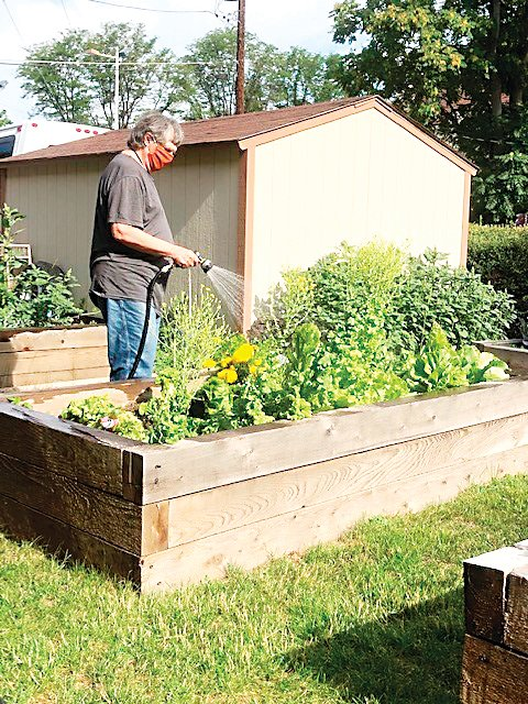 A resident waters the plants in the garden box at Senior Housing Options' Park Hill Assisted Living facility. Senior Housing Options will use its S.E.E.D. funding to install similar garden boxes at Olin Hotel apartments in Capitol Hill.