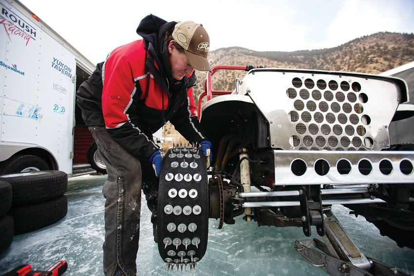 Mark Lannerd replaces a set of studded tires with the long metal spikes of the cheater tires for the next ice race competition on Georgetown Lake on Saturday.