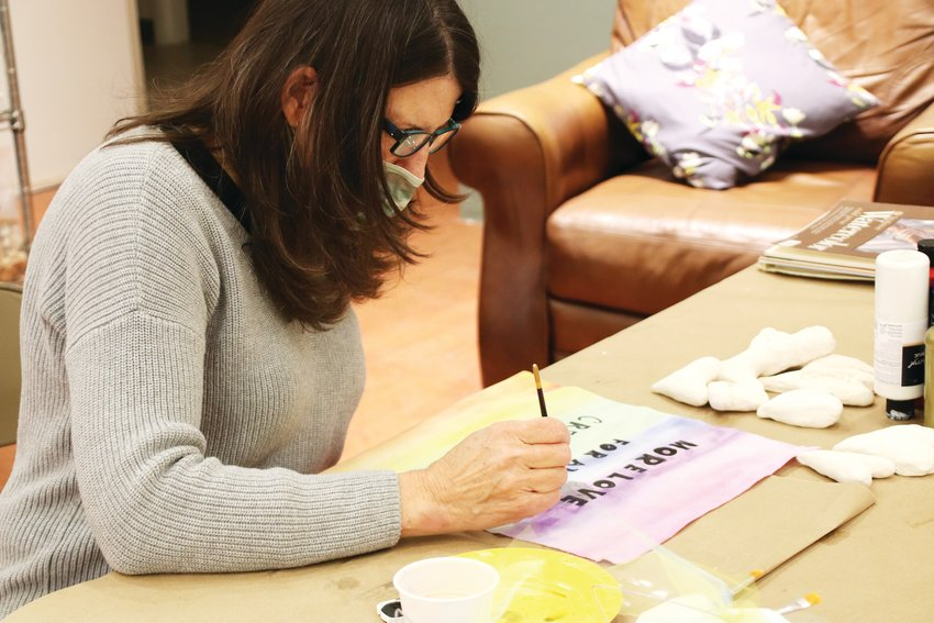 "Mar Knight-Hall, a member of the SoSu Artist Collective, works on a ""flag of hope"" on Feb. 4 at the group's studio at The Streets at SouthGlenn. Her flag is intended to advocate for ""more love and compassion for animals,"" Knight-Hall said."