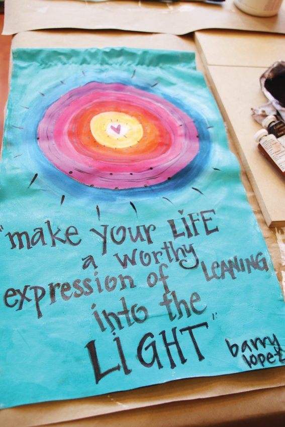 "Another of SoSu Artist Collective's ""flags of hope."" It bears a quote that reads, ""Make your life a worthy expression of leaning into the light."""