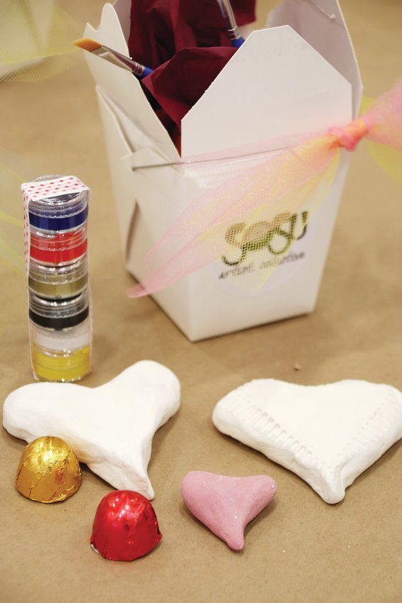 "The contents of one of the ""valentine take-and-make boxes"" that SoSu Artist Collective made for patrons. Usually, the group holds an in-person workshop to help people decorate clay hearts, but this year, patrons are picking them up or receiving them by delivery. The boxes include clay hearts, paints and chocolates."
