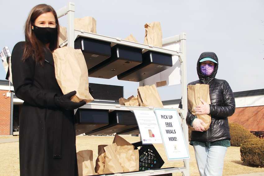 Littleton Public Schools nutrition services director Jessica Gould, left, and nutrition supervisor Sarah Kinney hold bags of food at a distribution site on Feb. 12. Food distribution during the pandemic could serve as a model for greater equity afterward, Gould said.
