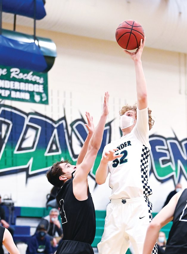 ThunderRidge's Zach Keller (32) uses his height advantage for the shot over Mountain Vista's Ben Lindauer (4). Keller added 13 points in the double-overtime league game. ThunderRidge ended up on top 80-71.