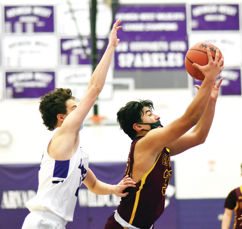 Golden sophomore Alan Acevedo (right) drives toward the basket during the first half Jan. 25 against Arvada West. The Demons took a 72-63 victory on opening night of the prep basketball season in Colorado.