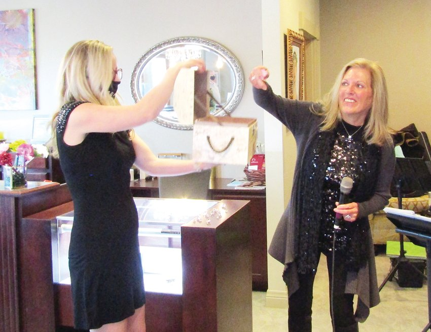 Suzanne Cannon, right, picks the winning ticket in the Sparkle for Special Needs fundraiser for the Evergreen Park & Recreation District's INSPIRE special needs program. Jenna McMenaman from Pandora John Properties held the box filled with 400 tickets.