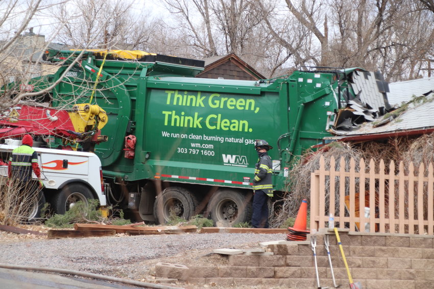 Denver firefighters prepare to extricate a Waste Management garbage truck from a home on South Julian Street in unincorporated Englewood on Feb. 24. Nobody was injured in the crash, but homeowner Dave Silva says he doesn't know what will become of his home.
