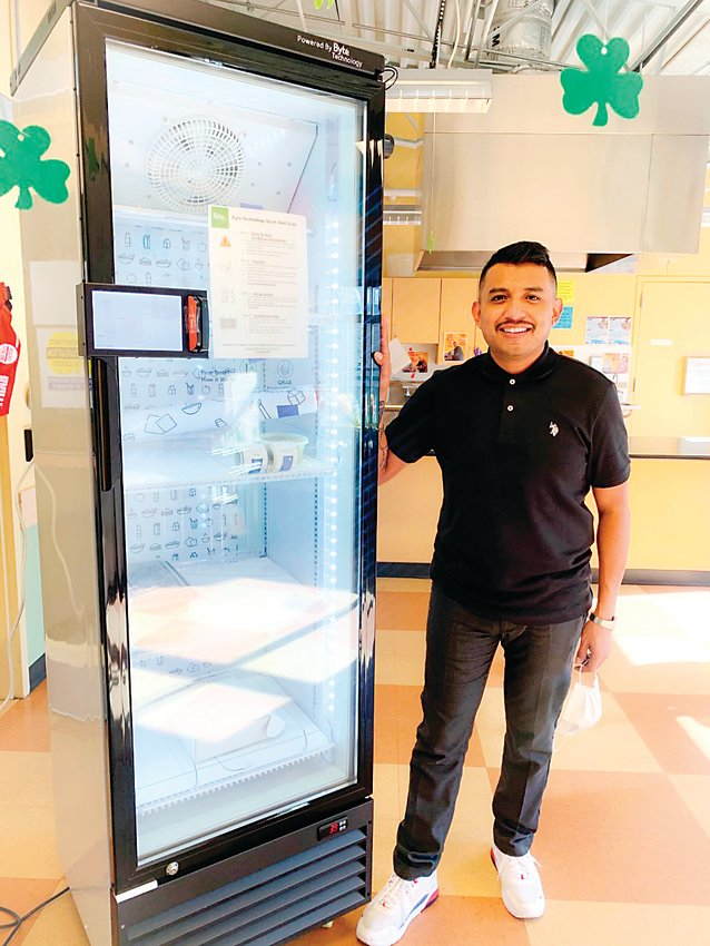 Alejandro Flores-Muñoz, co-owner of the food truck Stokes Poke and a ghost kitchen called Combi Taco, stands next to his new smart refrigerator. The refrigerator will allow Flores-Muñoz to expand his businesses, but also build community by partnering with other local micro-restaurant concepts to stock the refrigerator.