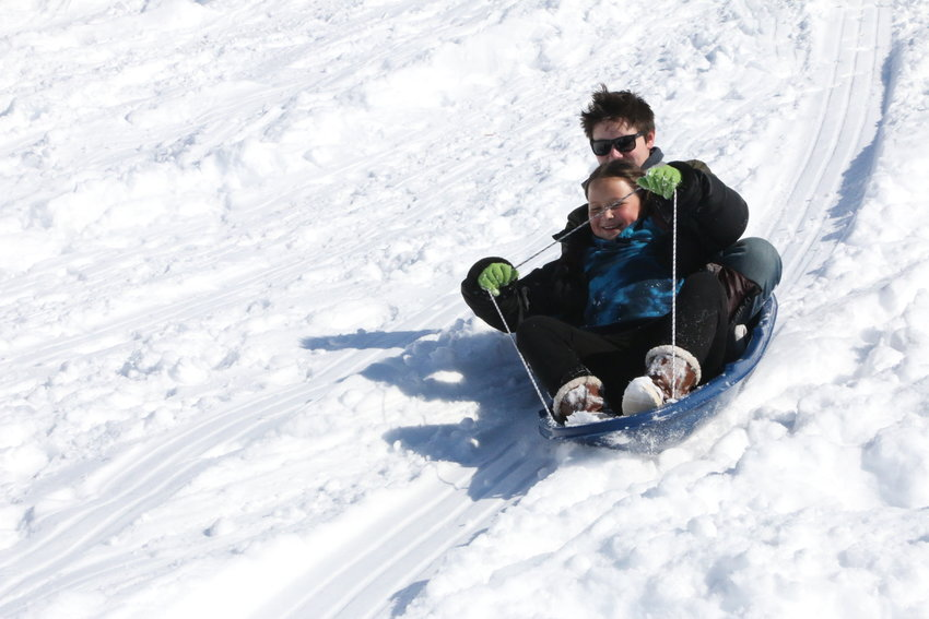 Caden and Emerson Haine take advantage of the snow day on the hillside at Indian Ridge Elementary School in Centennial.