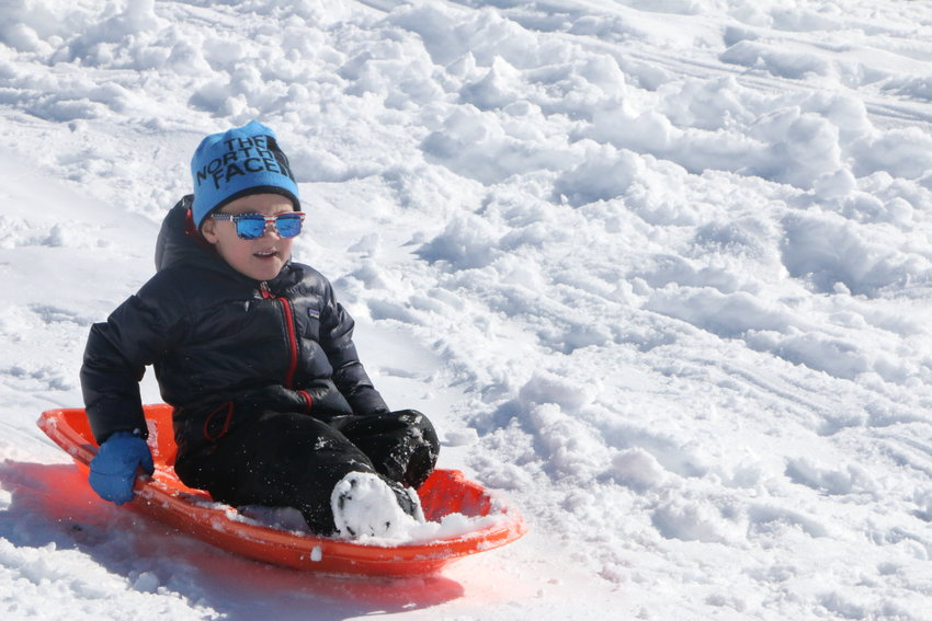 Enjoying the snow day, 6-year-old Evan Jensen rides the hills in style in Centennial.
