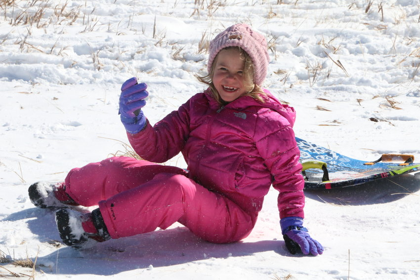 Mia Sikora, 7, takes a dive, landing upright with a smile on a hillside off Founders Parkway in Castle Rock.