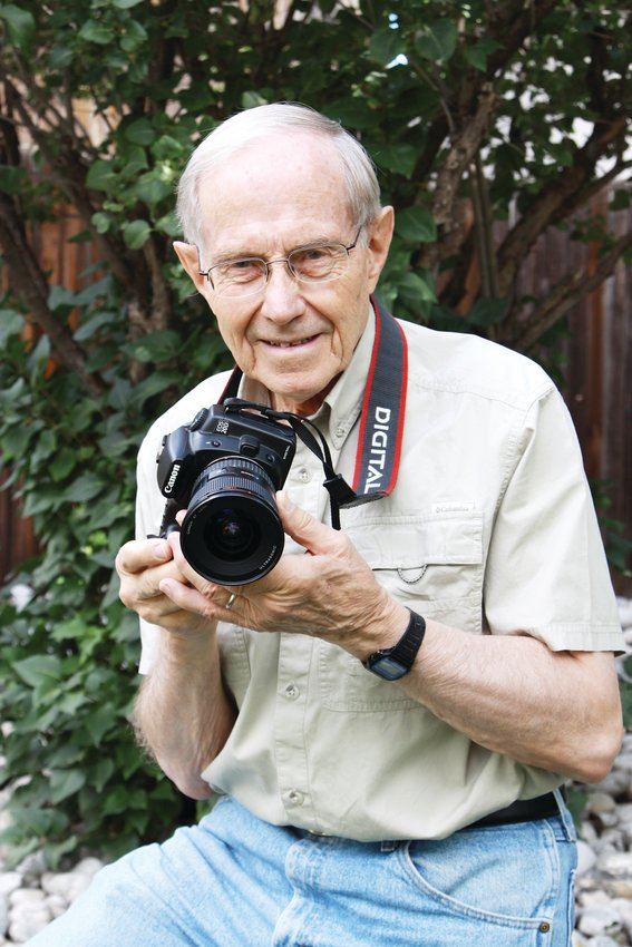 Portrait of Lowell holding a camera.