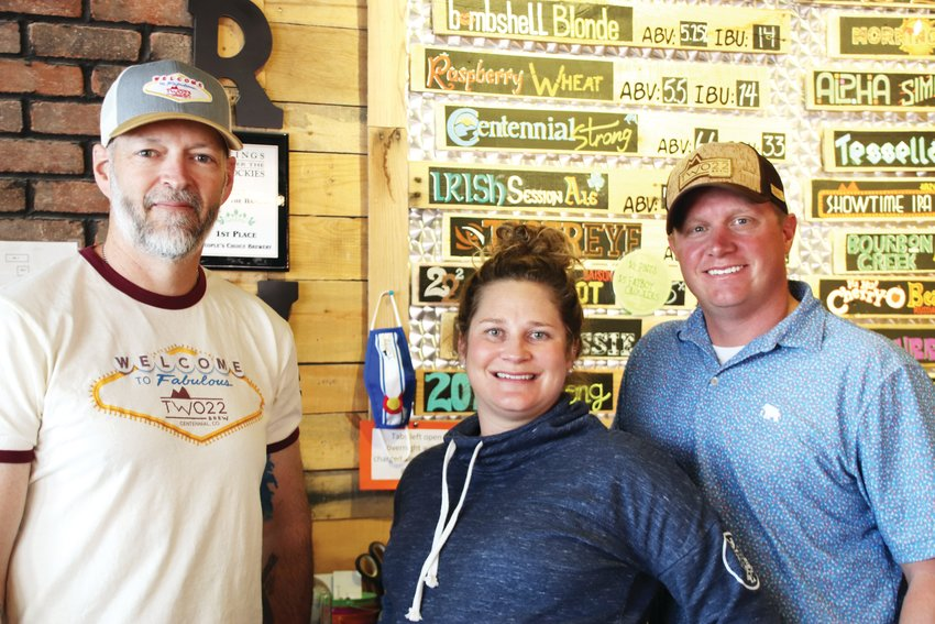 From left, Matt Cobb, taproom manager, and Paige Schuster and Marcus Christianson, owners of Two22 Brew, stand March 8 at the brewery in east Centennial. At Two22 Brew, $2.22 of every $10 of profit goes directly to certain Colorado nonprofits.