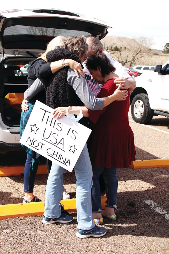 A group of attendees at a March 9 rally in Castle Rock huddle for a prayer. The rally took place before and during a county commissioner meeting.